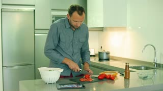 Man cutting tomato in the kitchen and smiling to the camera