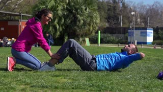 Man doing sit-ups and woman helping, slow motion shot at 240fps