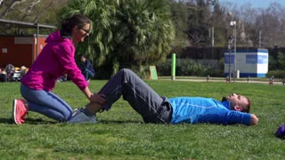 Man doing sit-ups and woman helping, slow motion shot at 60fps