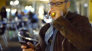 Man drinking beer and texting on smartphone in the cafe, steadycam shot