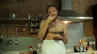 man drinking coffee and finishing his sandwich in the kitchen