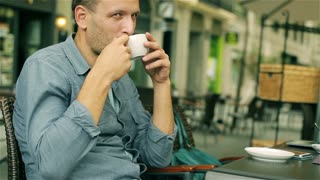 Man drinking coffee and looking to the camera in tha cafe, steadycam shot