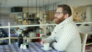 Man drinking coffee in the restaurant and smiling to the camera
