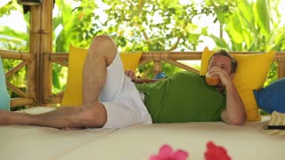 Man drinking juice and resting on bed in the garden