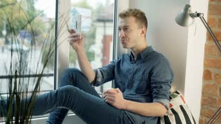 Man eating apple and having a videocall on smartphone
