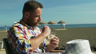Man eating ice creams on the beach and smiling to the camera, steadycam shot