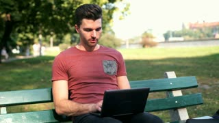 Man finish using laptop and relaxing while sitting on the bench in the park
