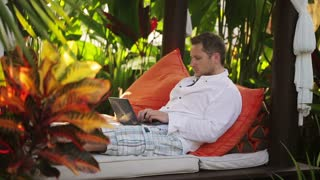 Man finish working on laptop and resting in the garden