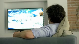 Man finishes watching television and turns it off
