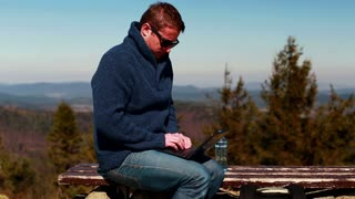 man finishing his work on a laptop and sitting on a bench in the mountainous