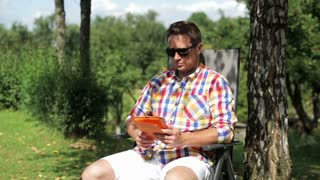 man finishing work on his tablet and relaxing in the garden