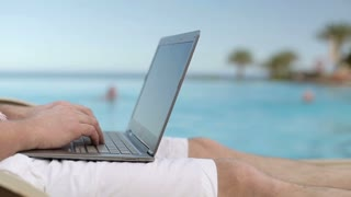 Man hands working with laptop by the swimming pool, steadycam shot