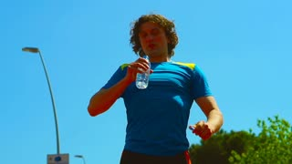 Man having a break while running and drinks water, steadycam shot, slow motion s