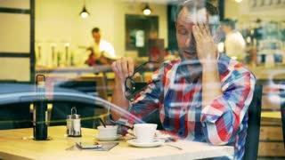 Man having headache and sitting in the restaurant, steadycam shot