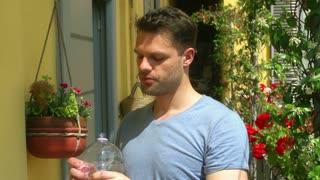 Man holding bottle and enjoying sun on the balcony, steadycam shot