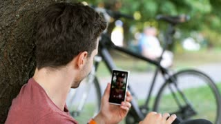 Man holding smartphone and doing photo of himself in the park
