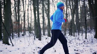 Man in blue sportswear running in forest, steady, slow motion shot at 240fps