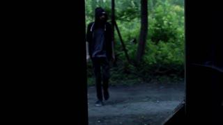 Man in hood walking inside abandoned building, steadycam shot