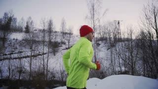 Man jogging alone on wintry day, steadycam shot, slow motion shot