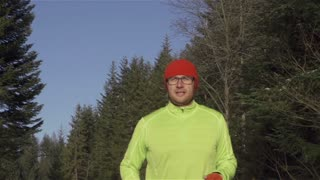 Man jogging in the forest, steadycam shot, slow motion shot at 240fps