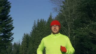 Man jogging in the forest, steadycam shot, slow motion shot