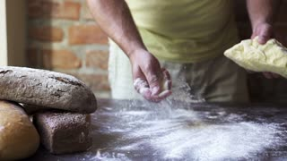 man kneading the dough and sprinkling flour, slow motion at 60 fps