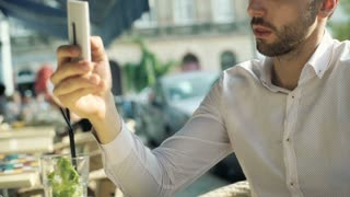 Man looking absorbed while browsing internet on smartphone