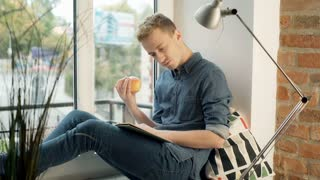 Man looking absorbed while reading book and throwing apple