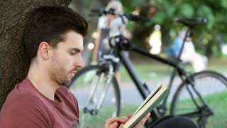 Man looking absorbed while reading book under the tree