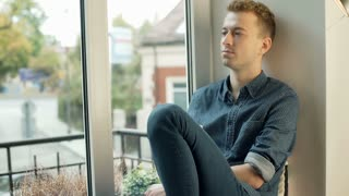 Man looking thoughtful while drinking coffee by the window