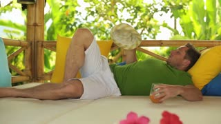 Man lying in bed and waving hat on hot day