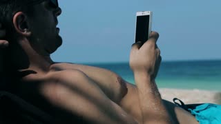 Man lying on sunbed and texting on cellphone, closeup