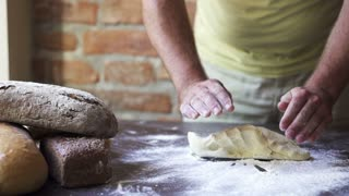 man mixing flour with dough on the table, slow motion at 240 fps
