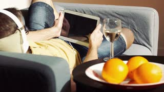 Man playing game on tablet and wearing headphones while lying on the sofa