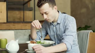 Man playing with food while sitting alone in the cafe and having some problems