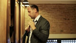 man putting his tie and a jacket into the wardrobe