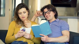 Man reading book and his girlfriend using smartphone, steadycam shot