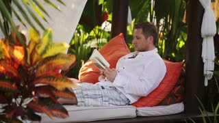 Man reading book and sitting in exotic garden