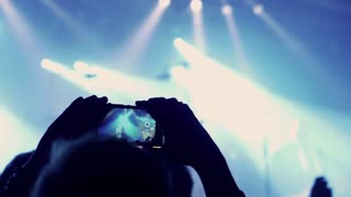 Man recording concert on cellphone and crowd having fun, steadycam shot