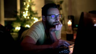 Man relaxing at his home and browsing internet on laptop