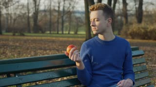 Man relaxing in the autumnal park and eating apple, steadycam shot