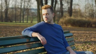 Man relaxing in the autumnal park and smiling to the camera, steadycam shot