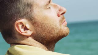 Man relaxing on the beach and having his eyes closed, steadycam shot