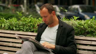 Man relaxing on the street bench and reading newspaper