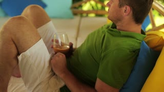 Man resting in bed and drinking juice, steadycam shot