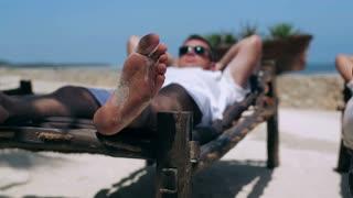Man resting on sunbed, steadycam shot