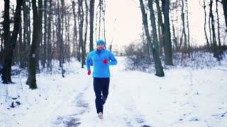 Man running on the path at winter, steadycam shot, slow motion shot at 240fps