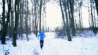 Man running on the path at winter, steadycam shot, slow motion shot