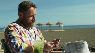 Man sitting in the cafe on the beach and texting on smartphone, steadycam shot