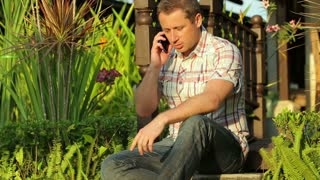 Man sitting in the garden and getting bad news while talking on cellphone